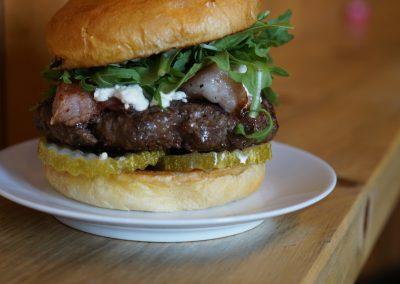 Delicious burger with Goat Cheese, Bacon, Pickles, Argula, Garlic Mayo